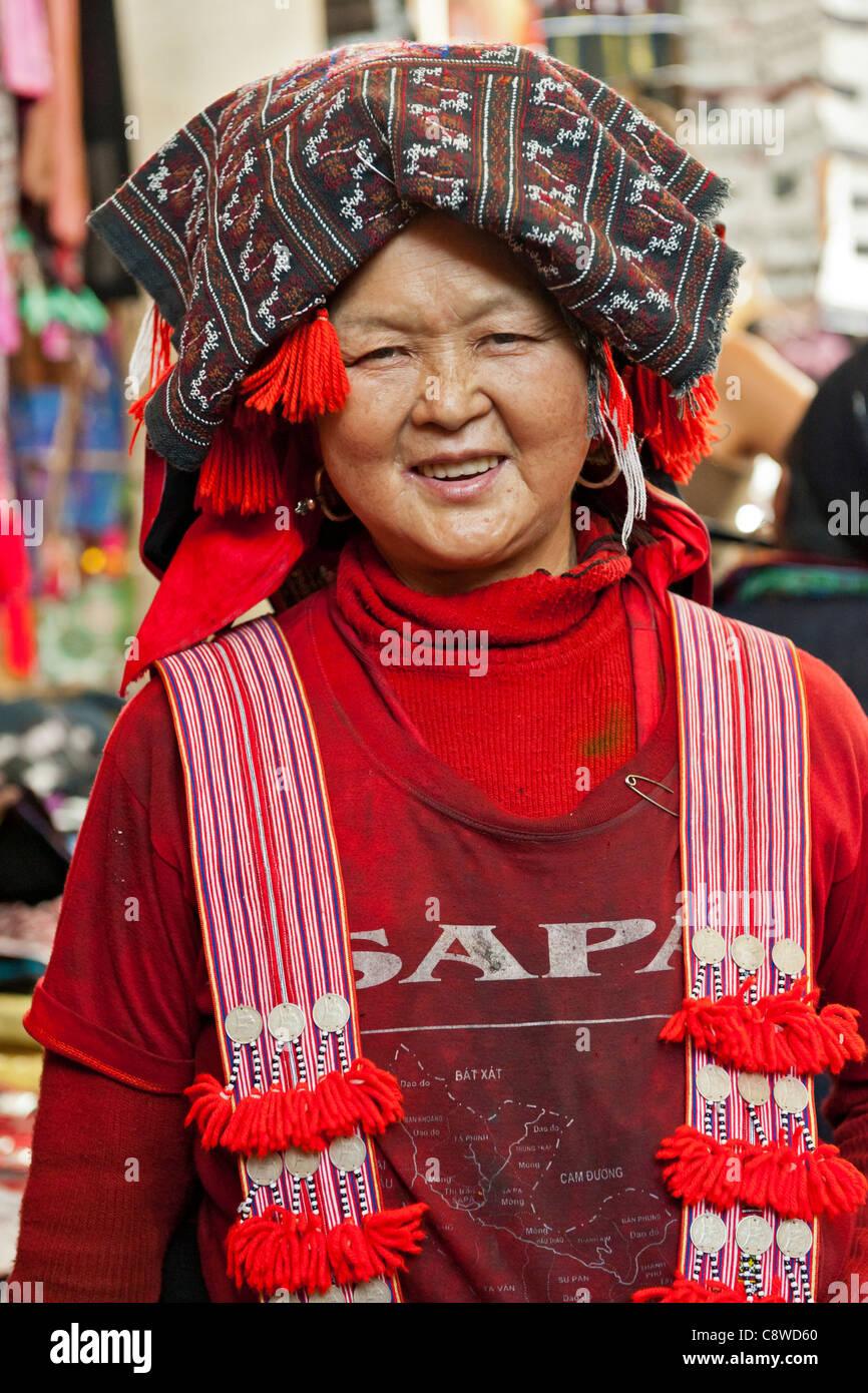 Red Dzao woman trader, wearing traditional headdress in Sapa tourist market. North Vietnam - Stock Image