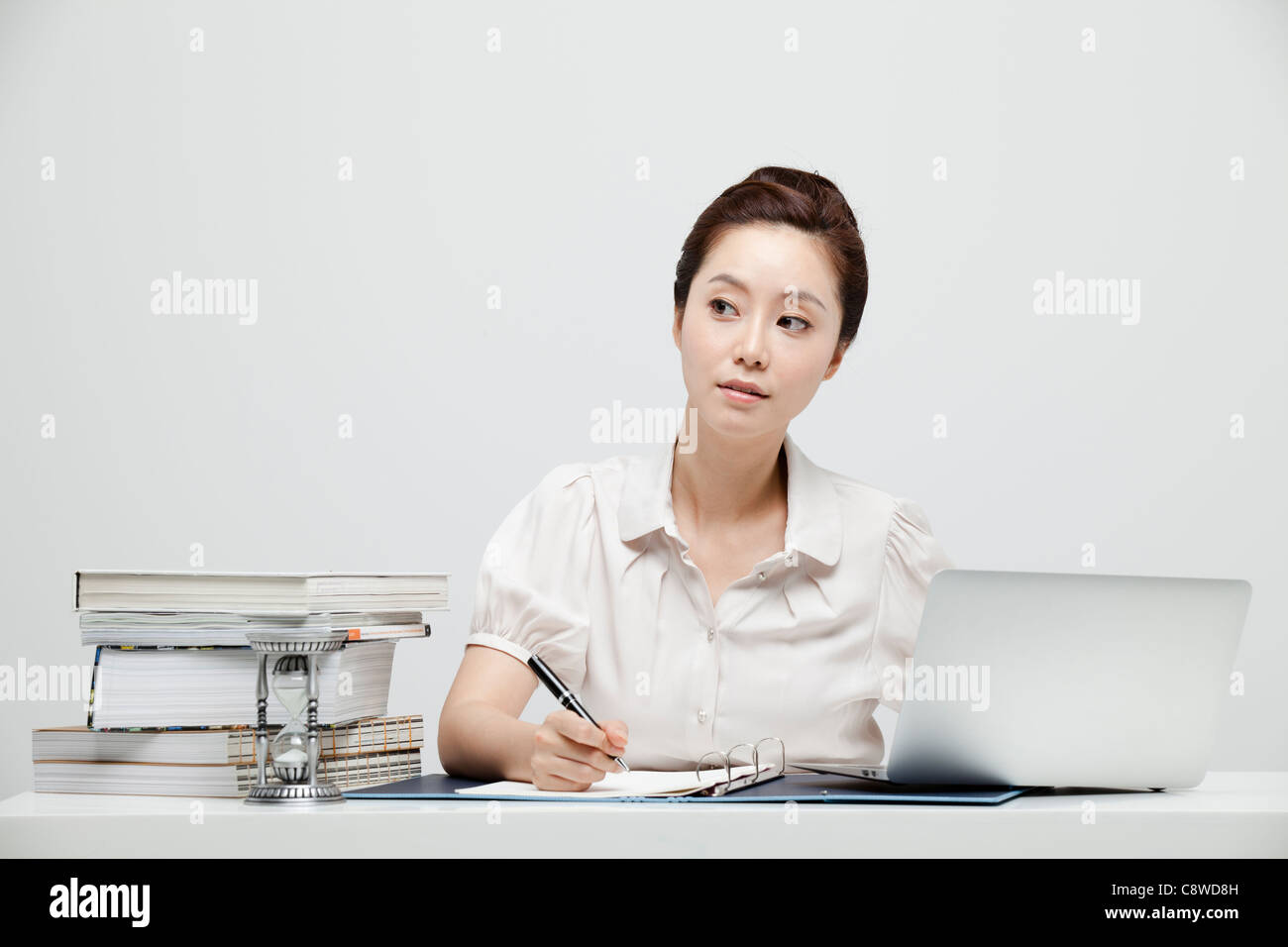 Asian Businesswoman At Desk Writing Document - Stock Image