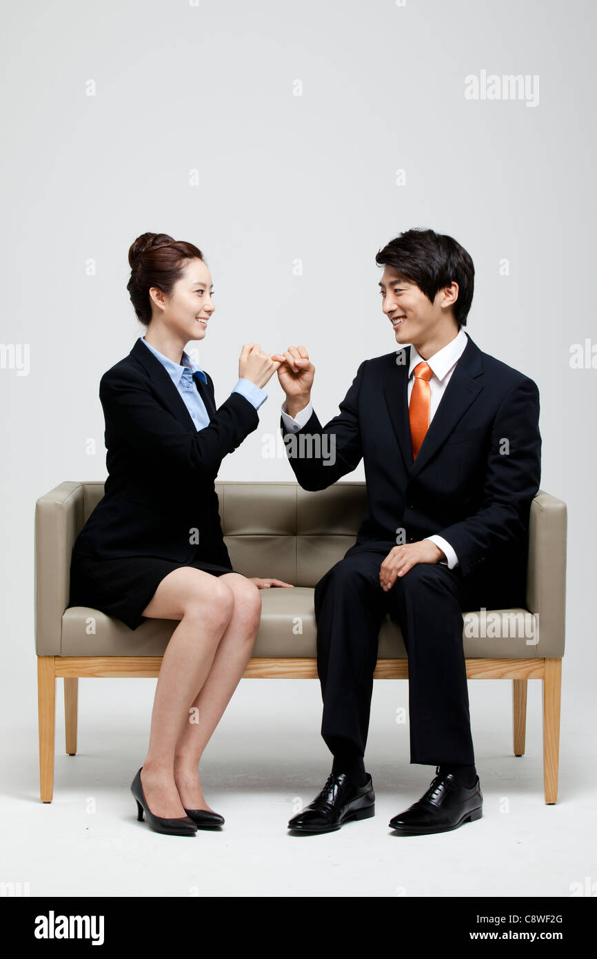 Asian Businessman And Businesswoman  Pinky-swearing And Sitting On Sofa - Stock Image