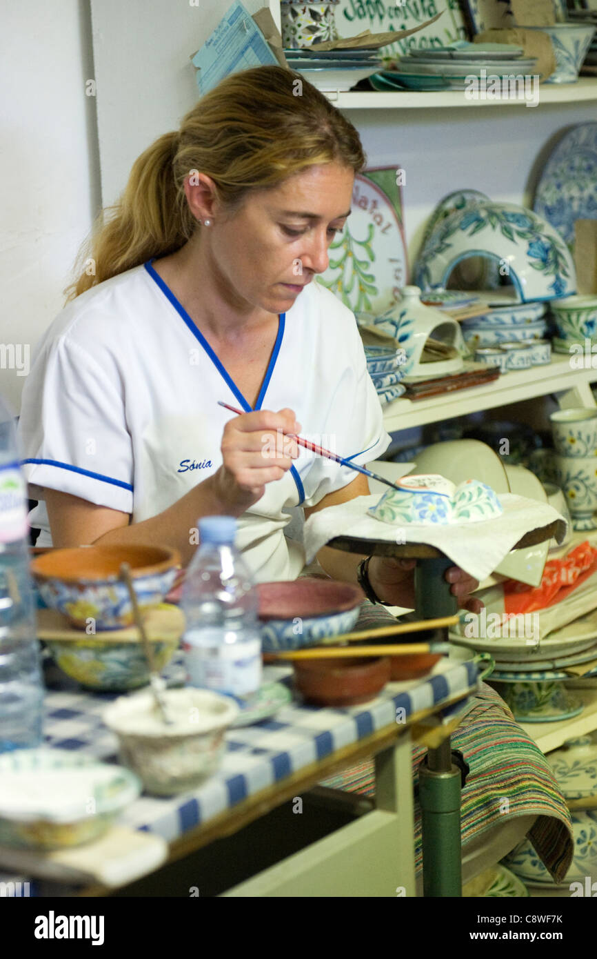 Portugal , Algarve , Olaria , Porches Pottery , attractive young blond lady hand painting bowl with floral design - Stock Image