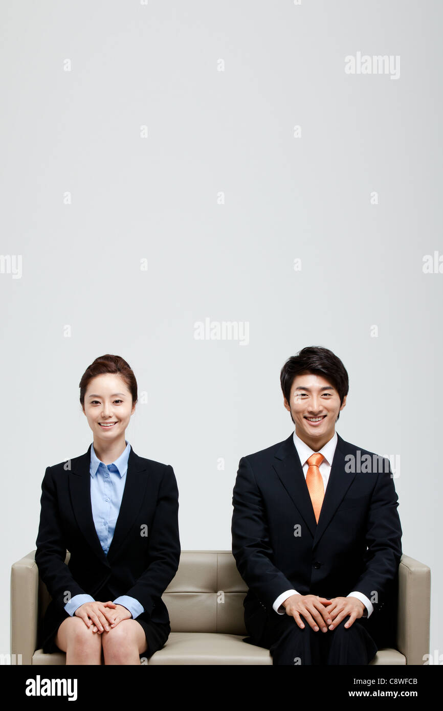 Asian Businessman And Businesswoman Sitting On Sofa Stock Photo