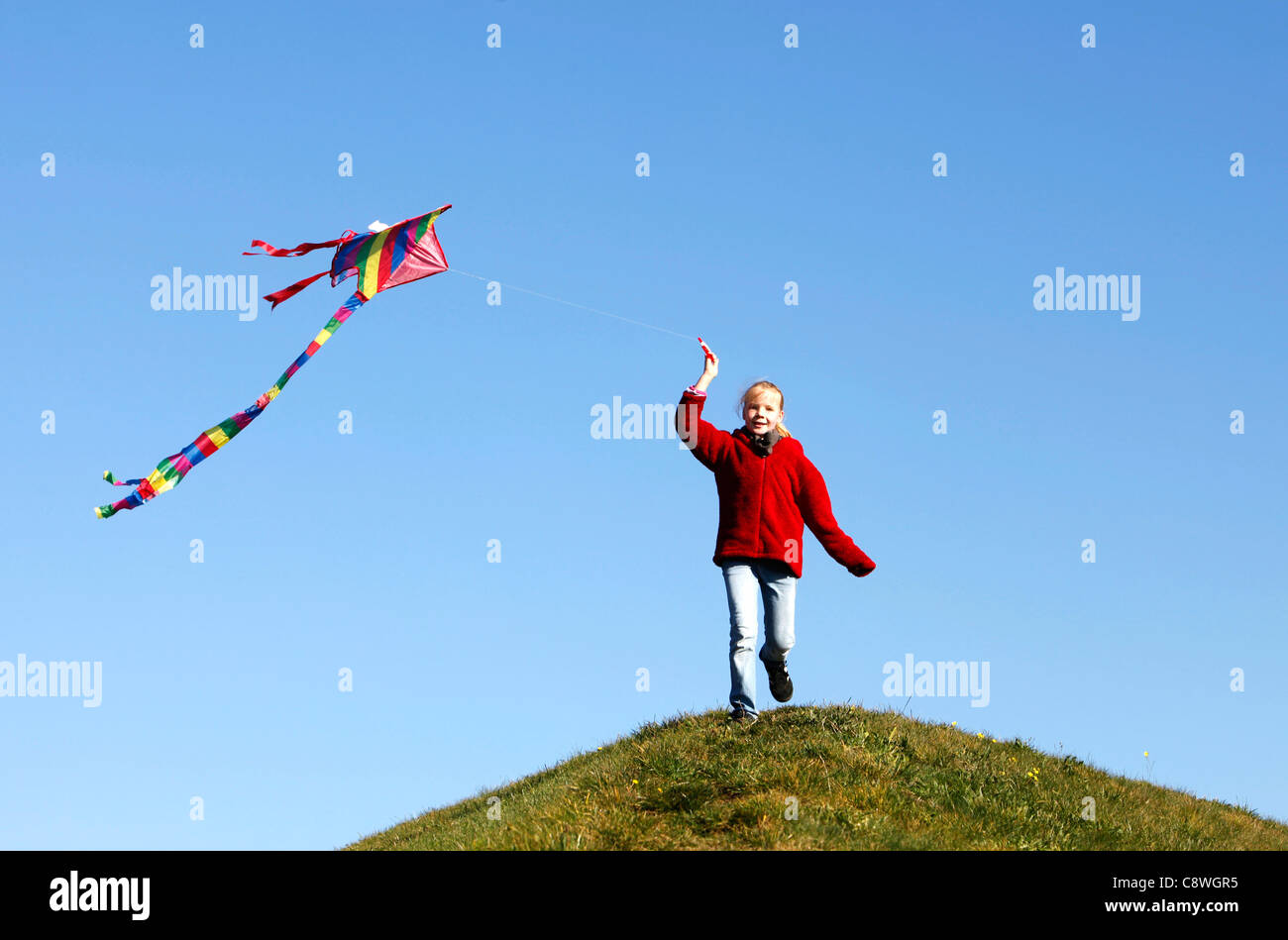 Girl, 10 years old, running with a kite, to let it fly. - Stock Image