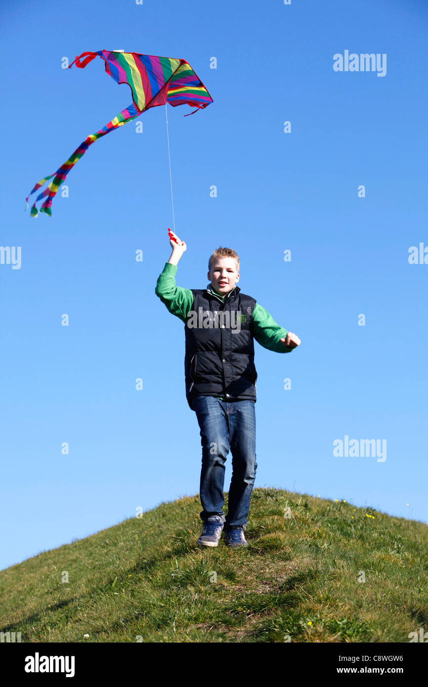 Boy, 13 years old, running with a kite, to let it fly. - Stock Image