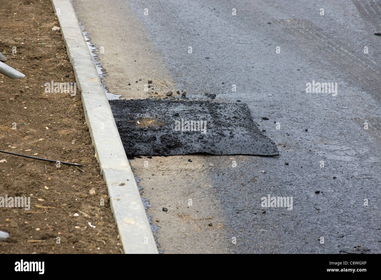 Road drain covered with a square of felt before the machine laying a new tarmac road surface reaches the area. - Stock Image