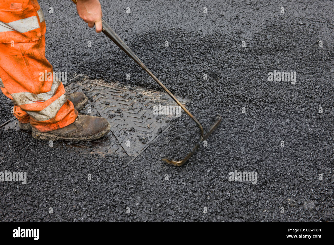 Asphalt being raked around a manhole cover to fill gaps in surface, of newly laid road, after protective felt removed. - Stock Image