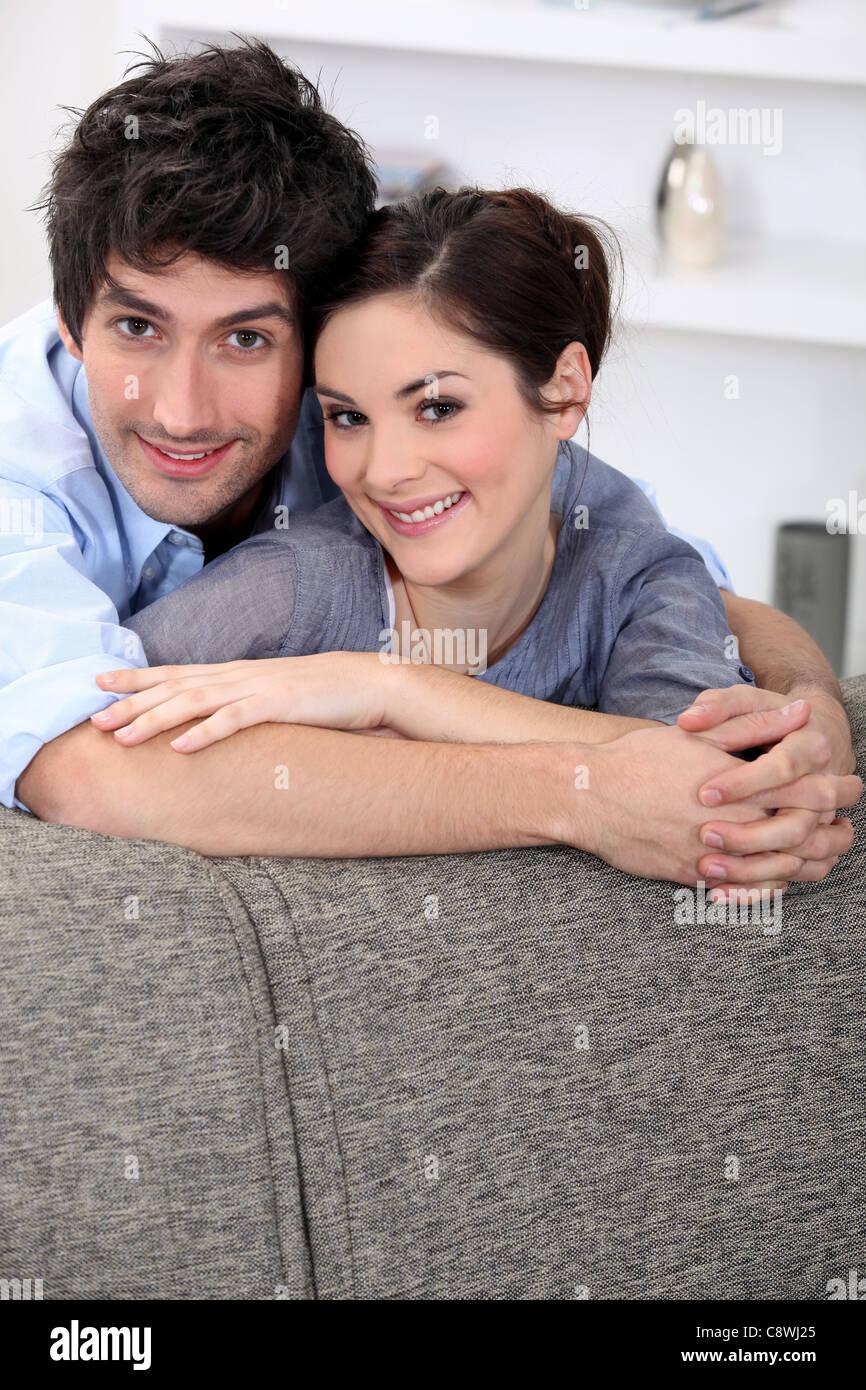 Couple hugging behind sofa - Stock Image