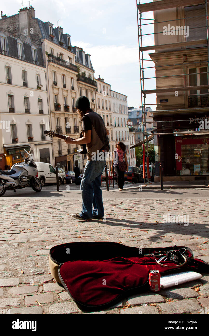 Busker in Paris, France playing guitar - Stock Image