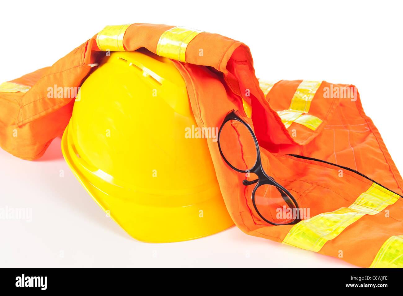Hard hat, reflective orange vest and safety glasses on white. - Stock Image