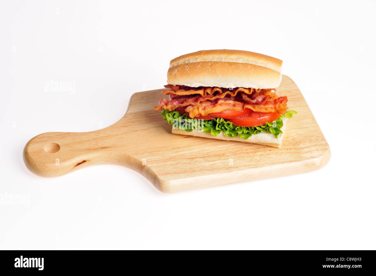 Bacon, Lettuce and Tomato BLT sandwich on a  bread roll on a wood cutting board on a white background. USA - Stock Image