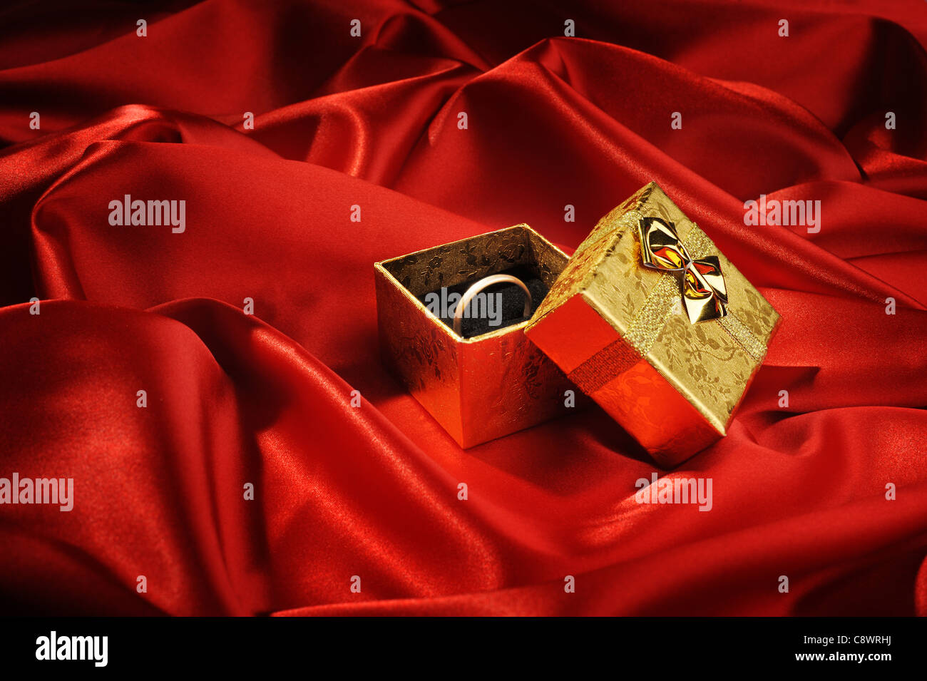 Gold boxes with a wedding ring on red silk - Stock Image