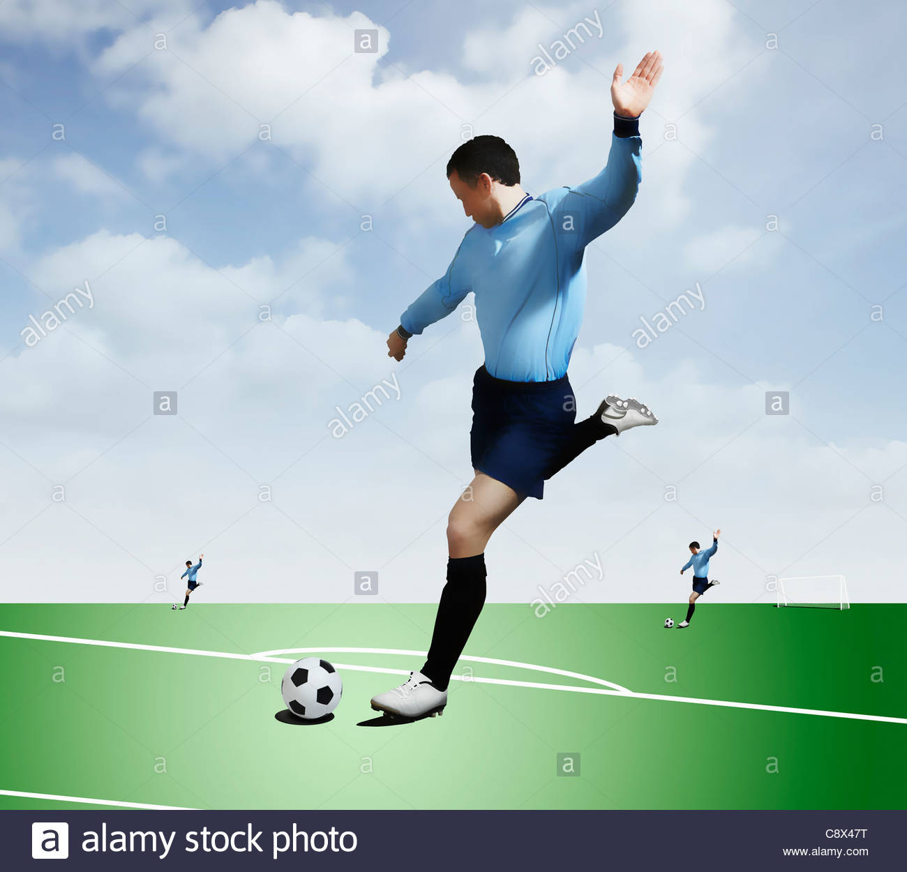 Man kicking soccer ball on pitch - Stock Image