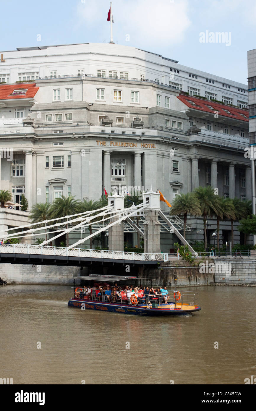 The Fullerton Hotel and Cavenagh Bridge with tourist boat, Singapore - Stock Image
