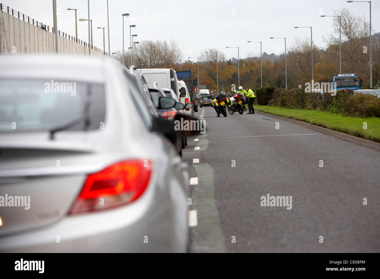 Police motorcycle officers clear debris from a road traffic accident in the outside lane of a dual carriageway in - Stock Image
