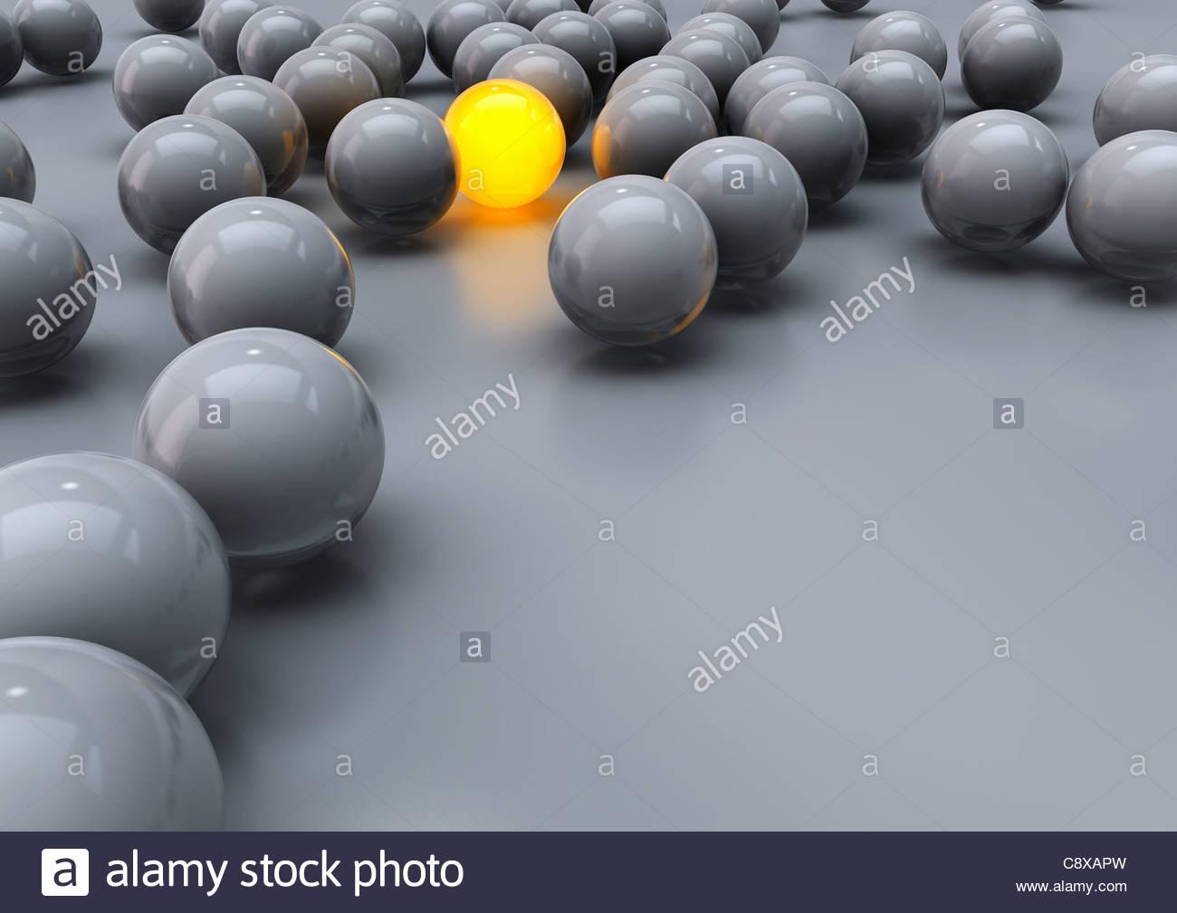 Glowing yellow ball among grey balls - Stock Image
