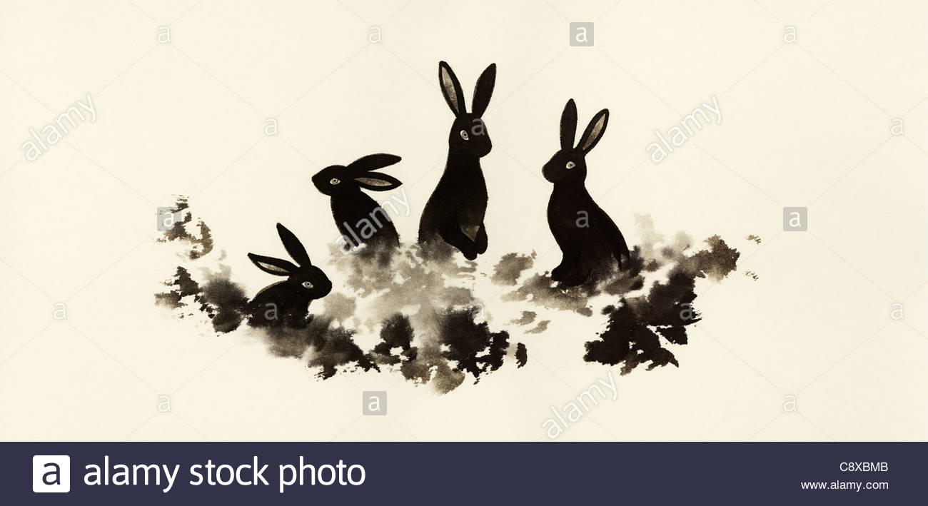 Rabbits sitting in grass together - Stock Image