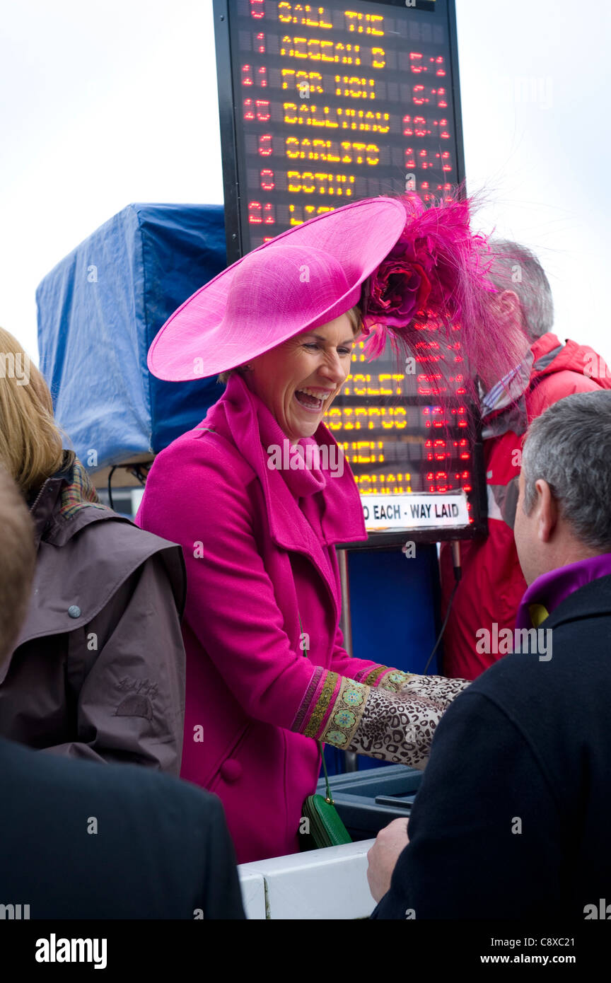 Female book maker dressed in a bright pink hat and matching coat taking a bet at Cheltenham horse races. - Stock Image
