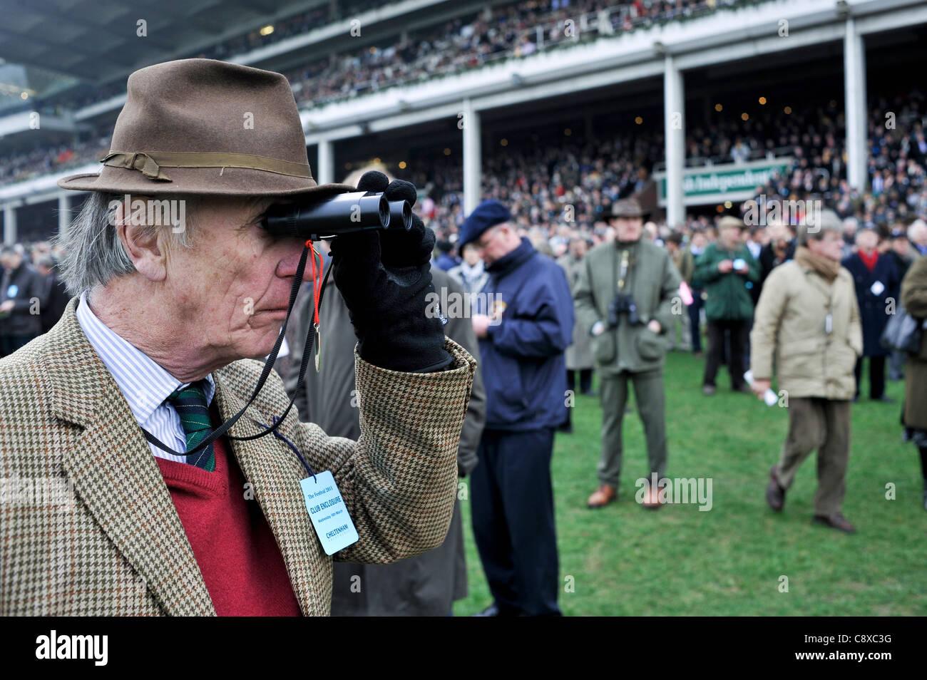 Elderly Man watching the horse racing at the Cheltenham Festival. England - Stock Image