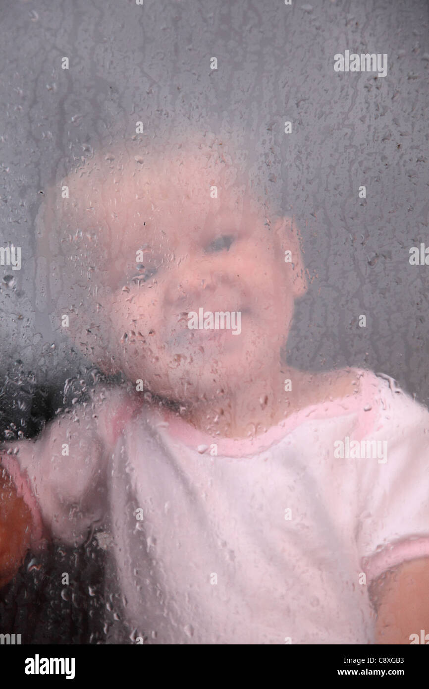 Adorable toddler watching the rain drops at the window - Stock Image
