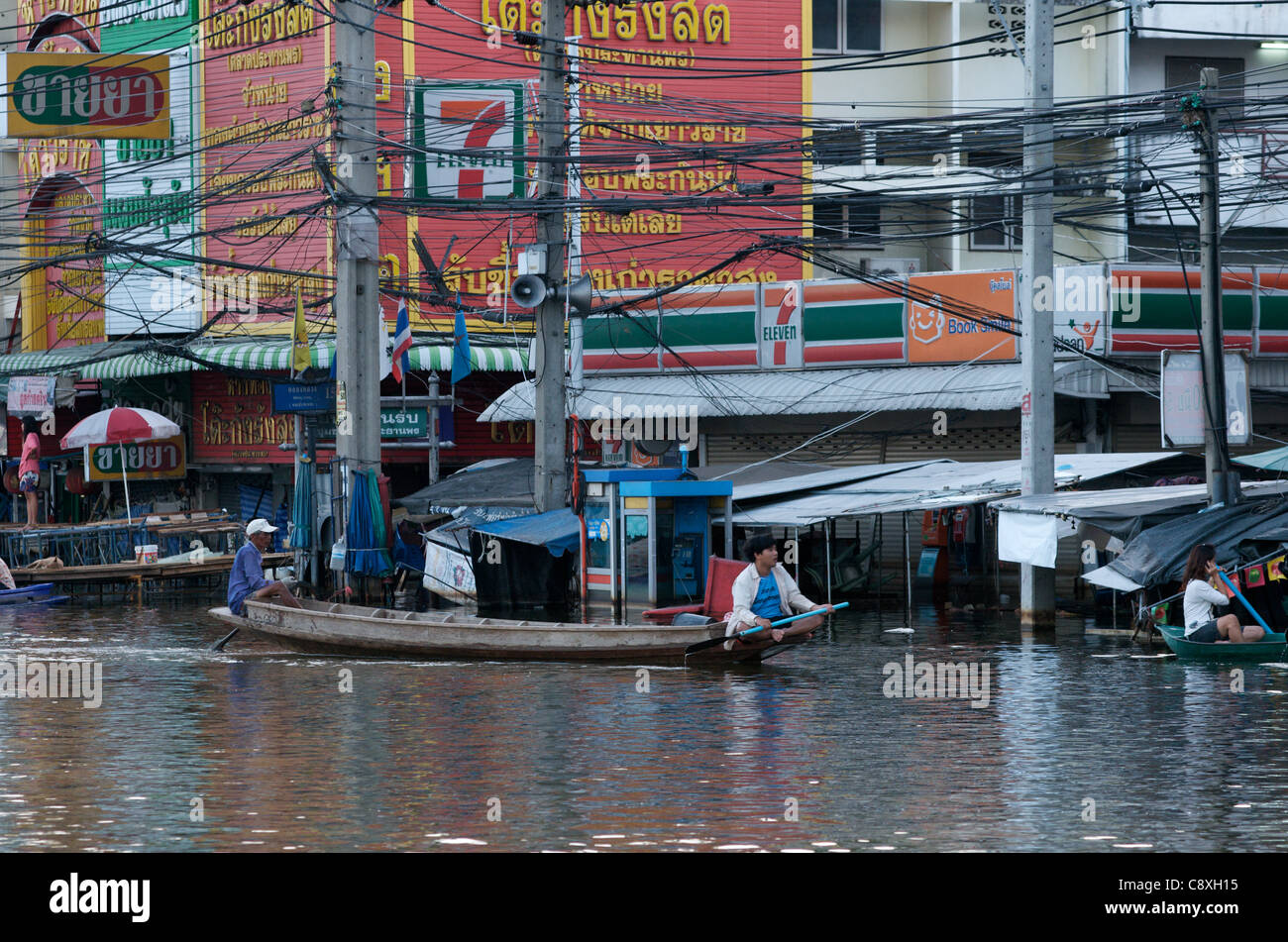 Thai men paddle boat past Flooded 7-11 in Rangsit, a