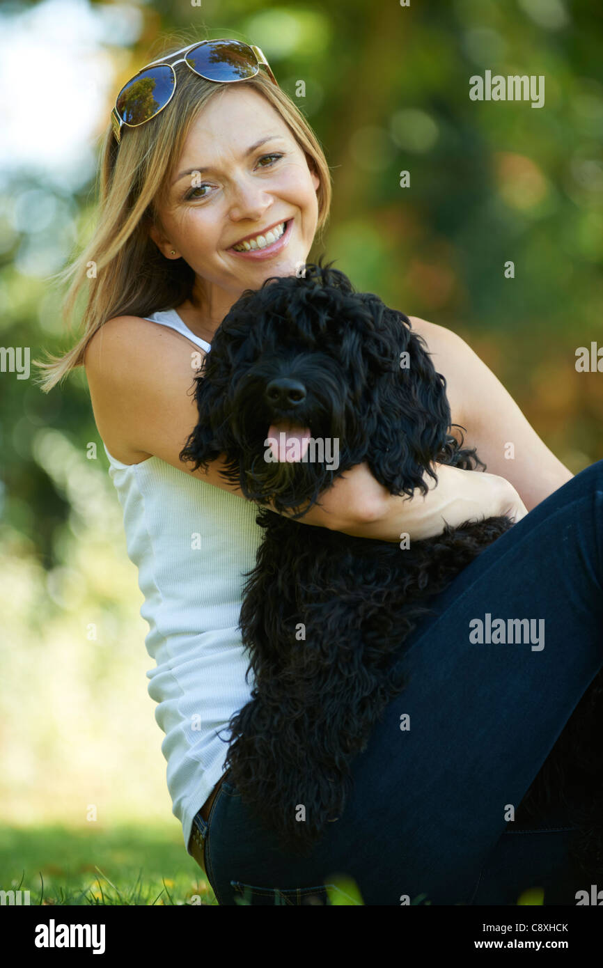 woman relaxing with black dog while on a walk in the park - Stock Image