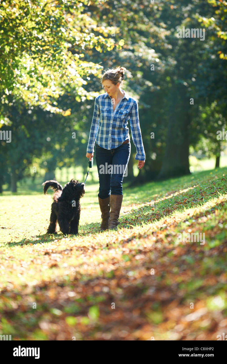 woman walking her black dog in the park on a sunny day - Stock Image