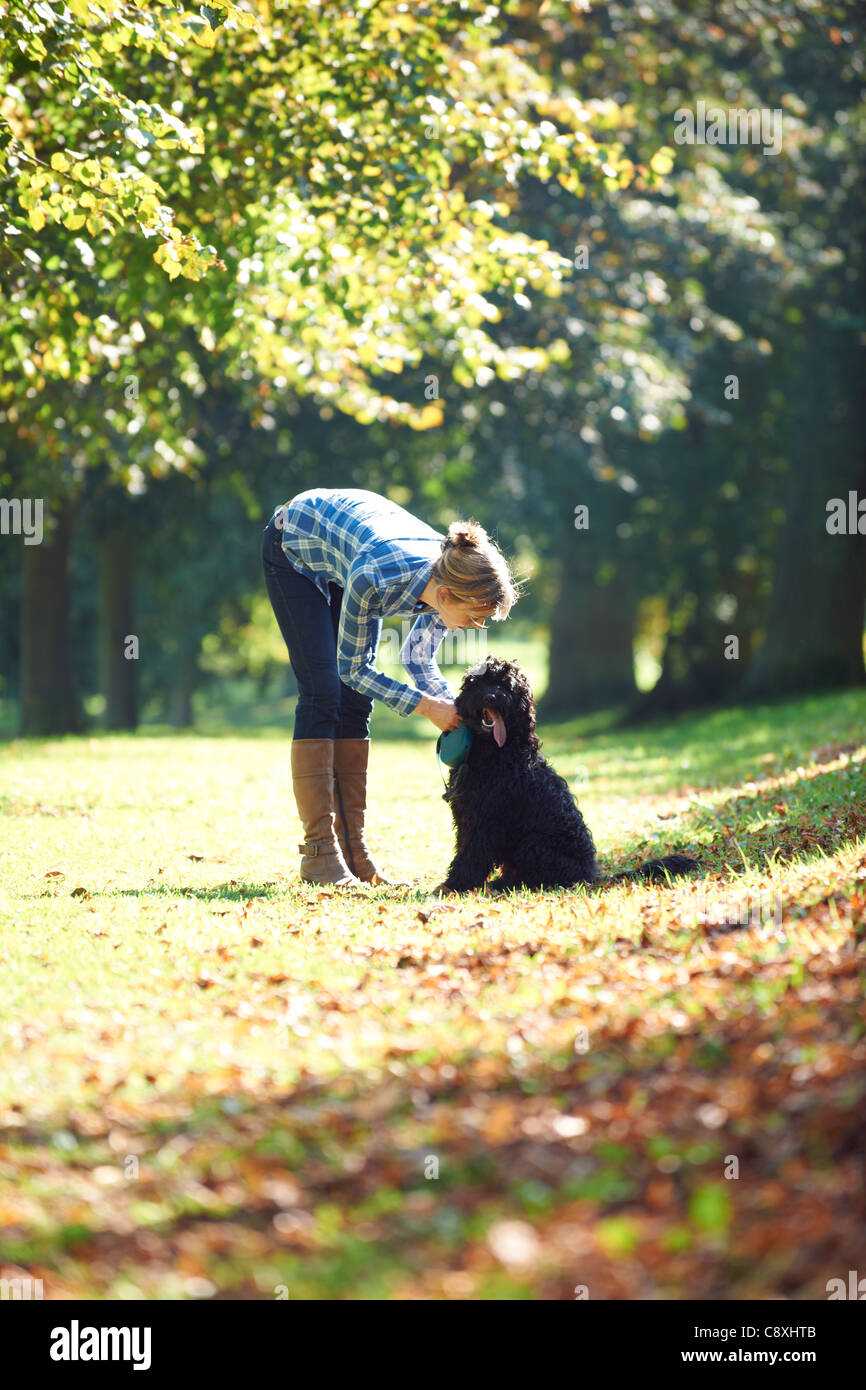 woman leaning over black dog on a walk in the park - Stock Image
