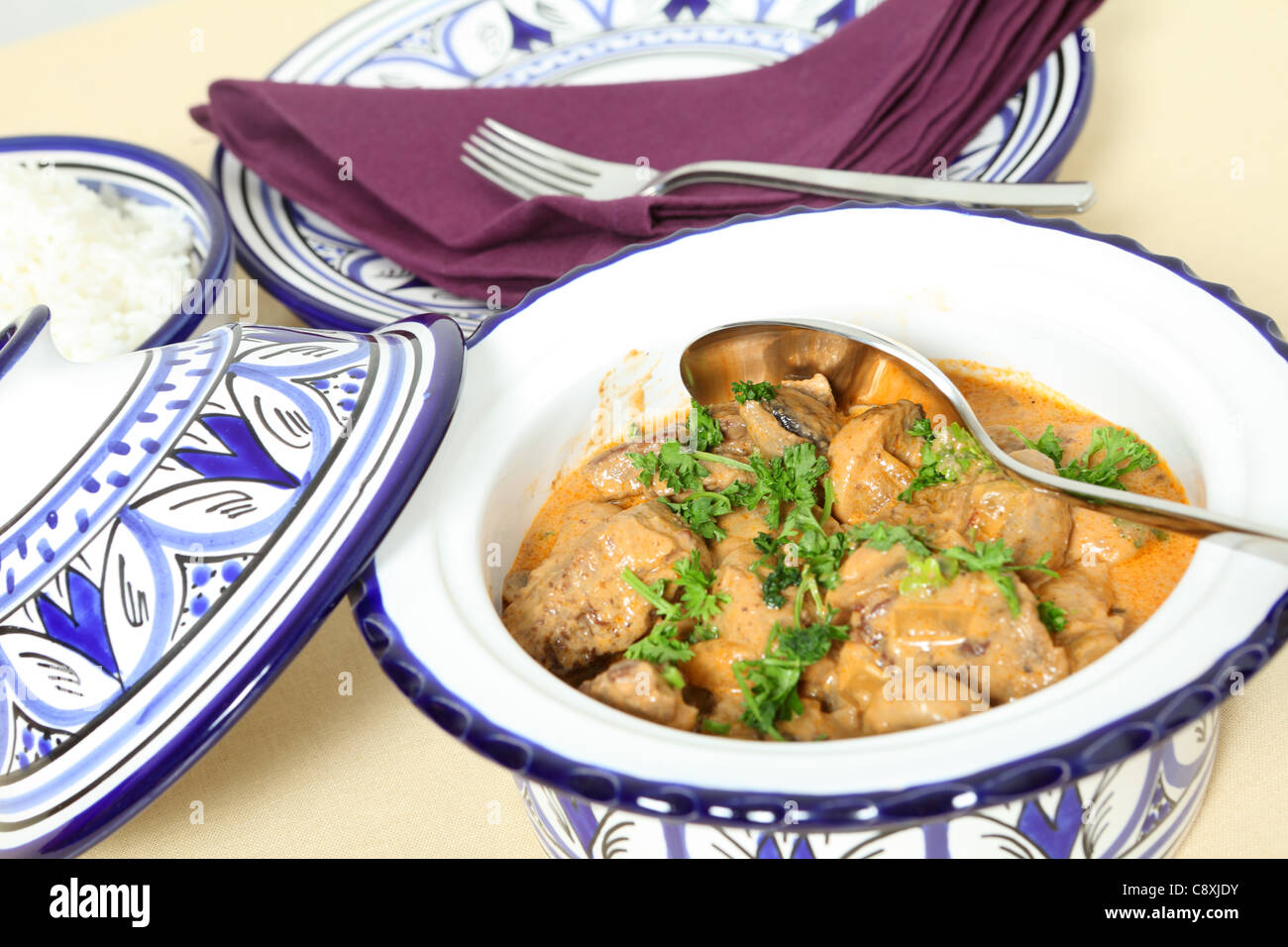 A bowl of beef stroganoff with white rice and a spoon on a table and dinner plates and forks behind, horizontal - Stock Image