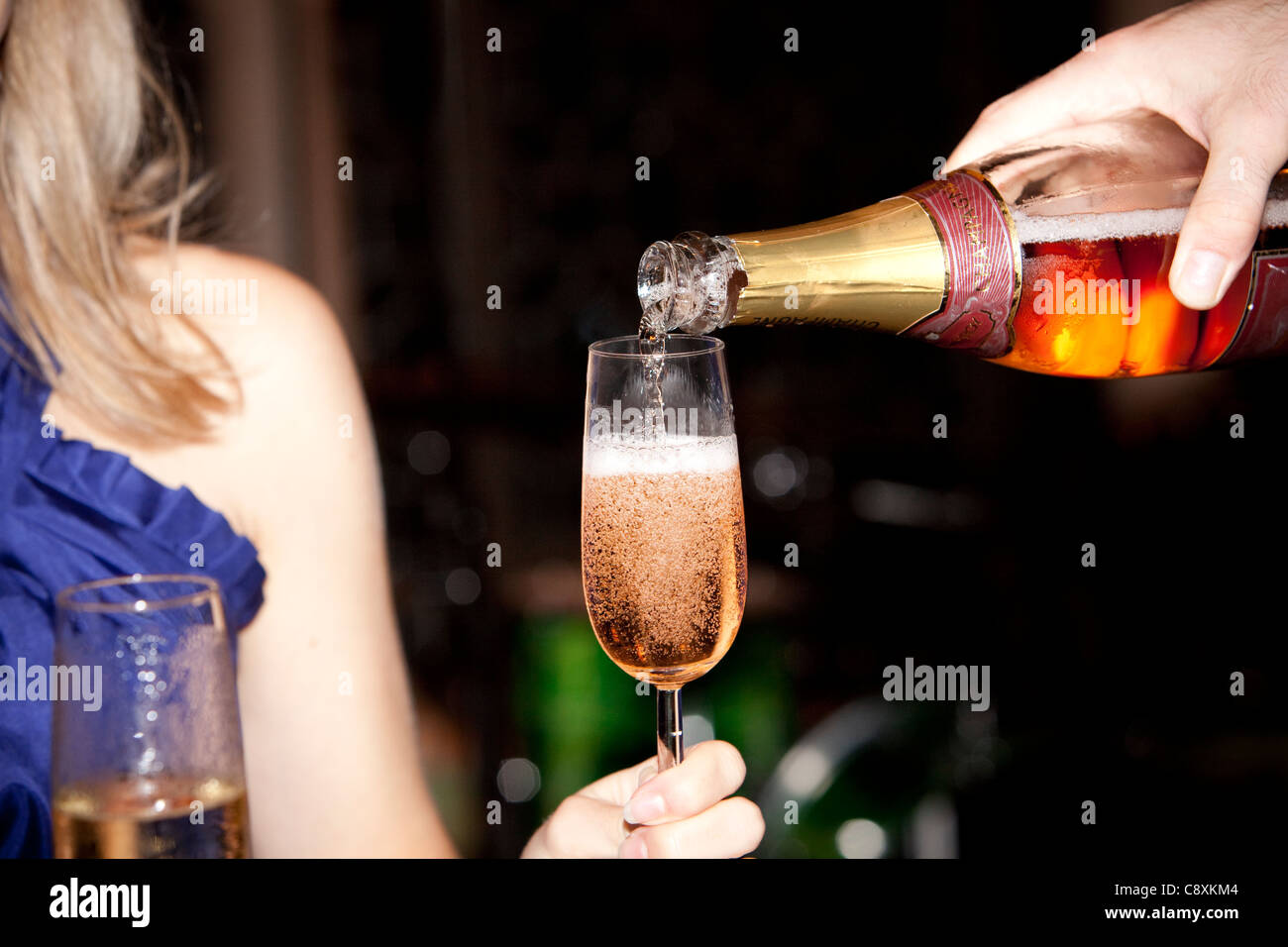 Pouring champagne into glass. - Stock Image