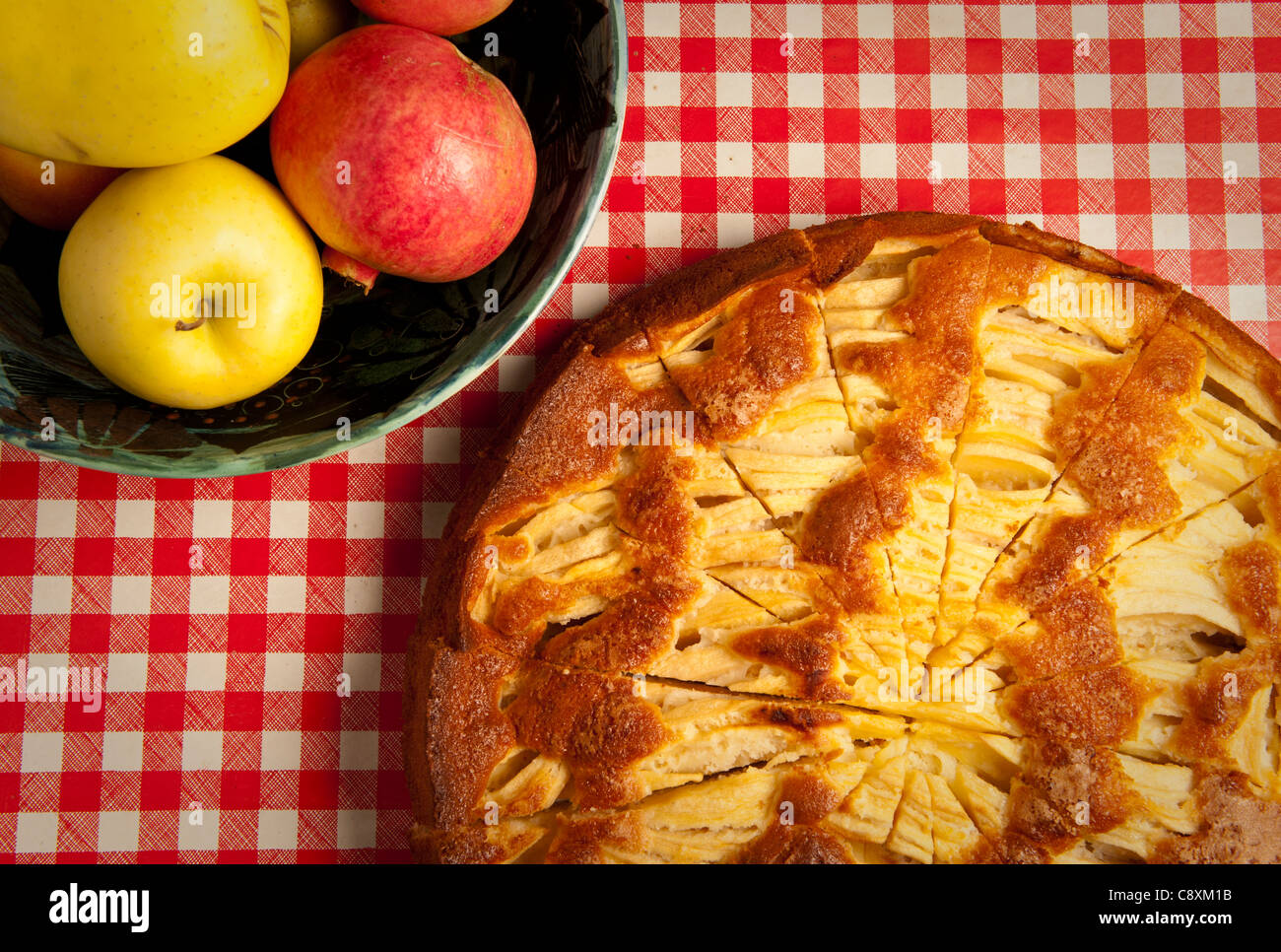 traditional Italian home made apple crostata on red and white checked table cloth, bowl of apples - Stock Image