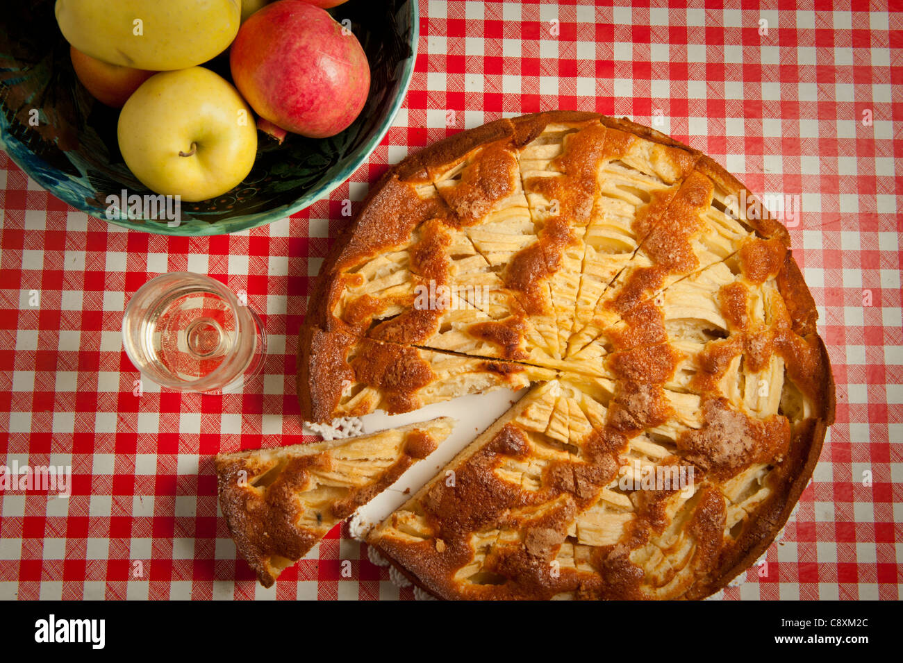 traditional Italian home made apple crostata on red and white checked table cloth, bowl of apples and glass of dessert - Stock Image