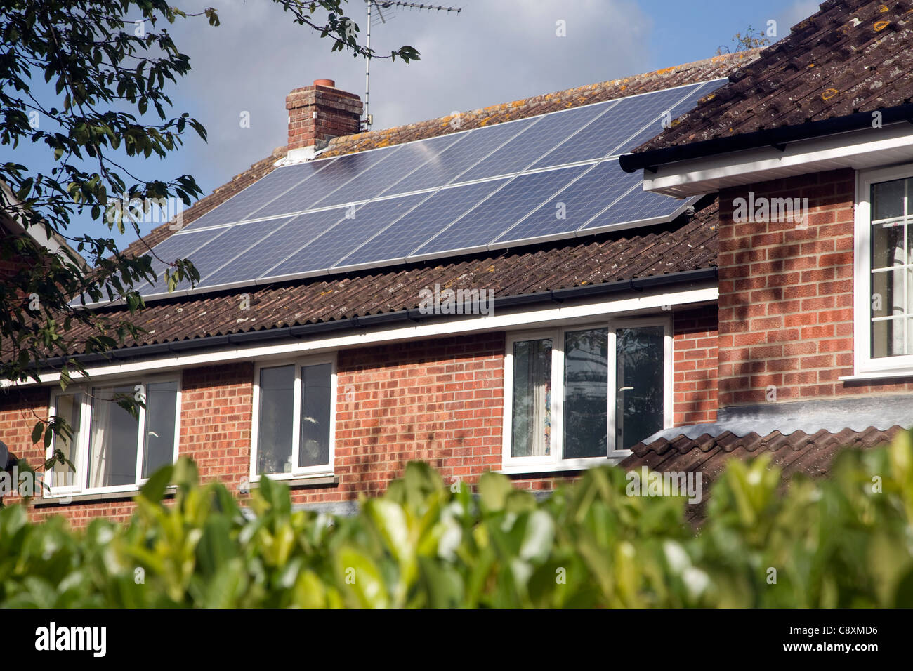 Large array of solar panels on domestic house roof - Stock Image