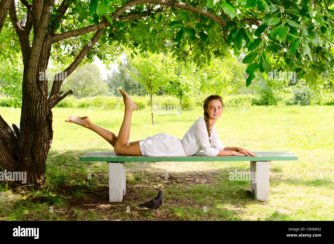 https://c8.alamy.com/comp/C8XMN2/pretty-barefooted-woman-is-laying-on-a-bench-under-the-green-tree-C8XMN2.jpg