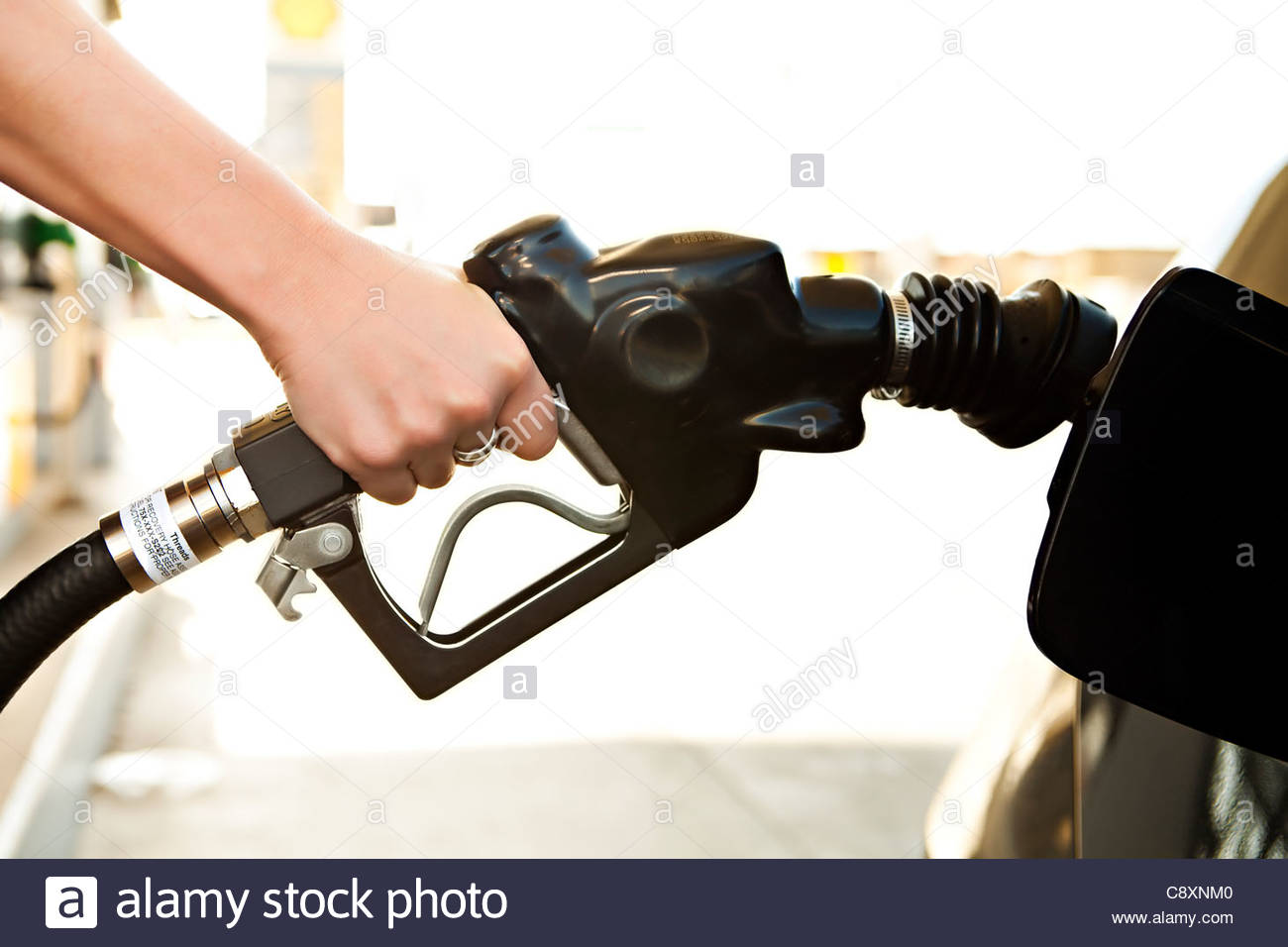 USA, California, Lawndale, Female hand inserting fuel pump into car gas tank - Stock Image