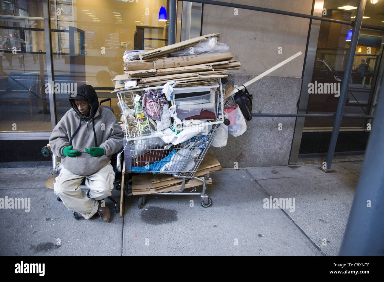 Homeless man with his possessions on 34th Street in New York City. - Stock Image
