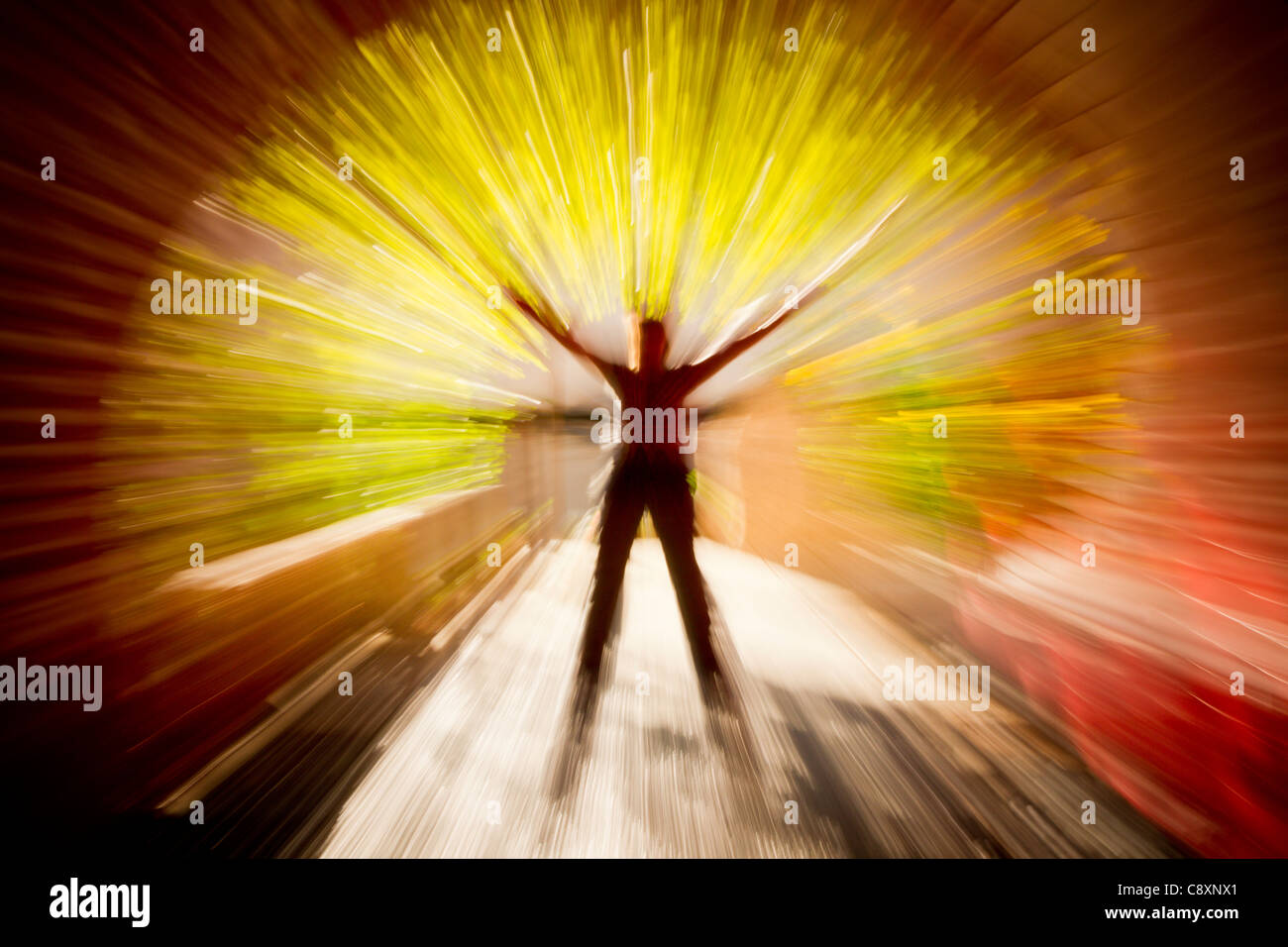 Abstract figure in tunnel with arms raised - Stock Image