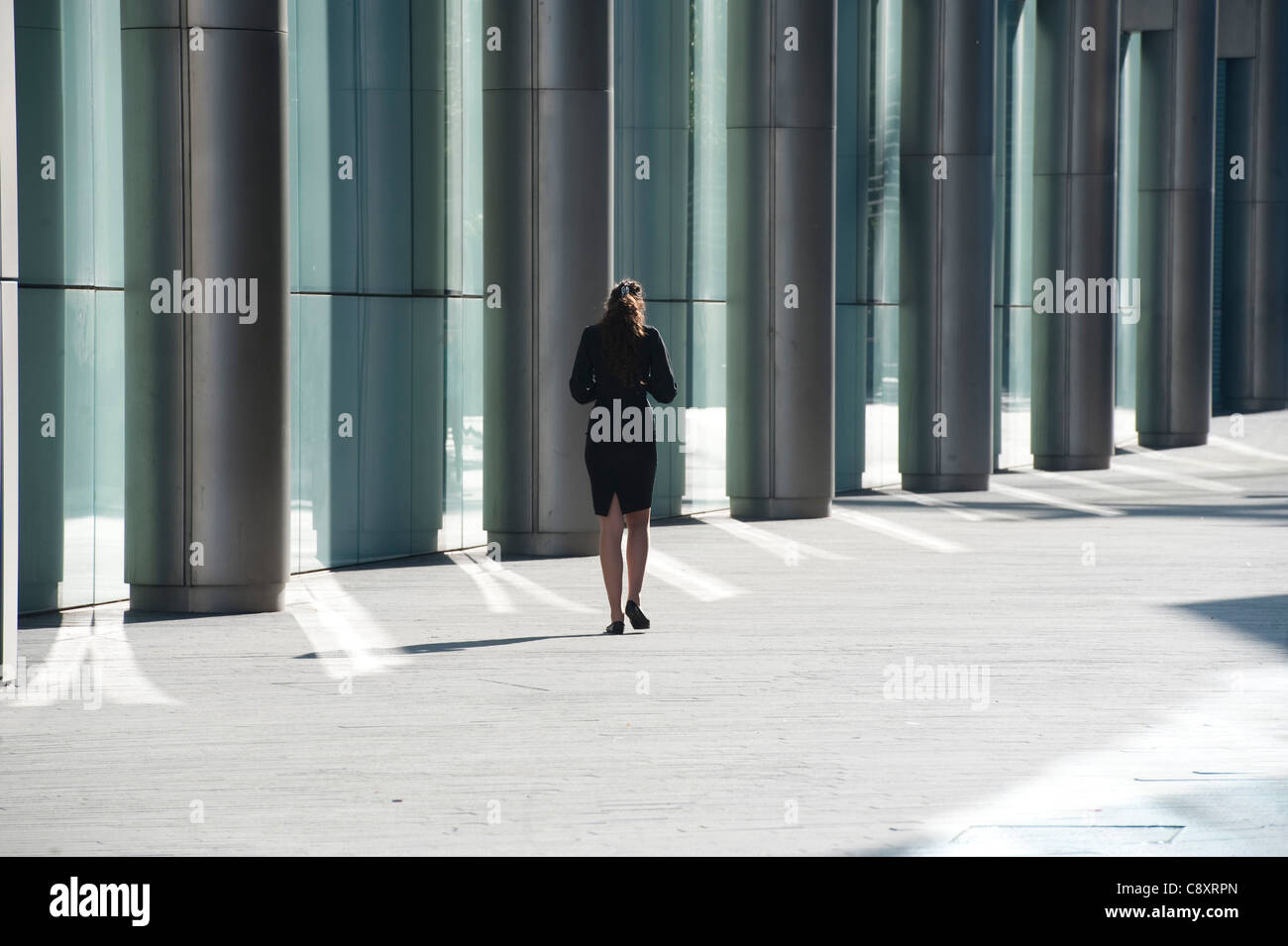 backview of woman near modern office building Central London - Stock Image