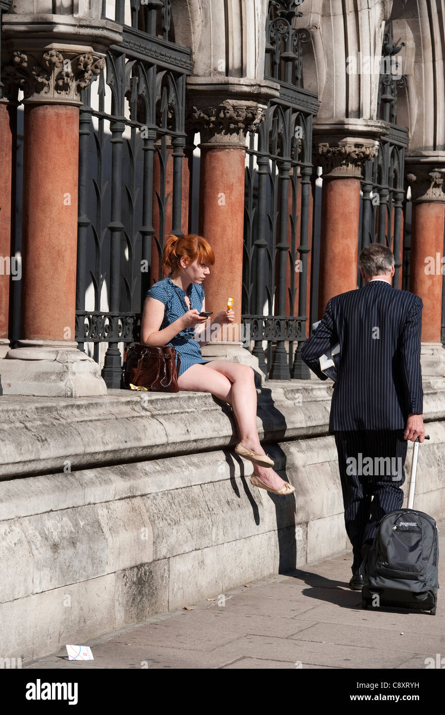 woman sits on wall eating ice cream on hot London day - Stock Image