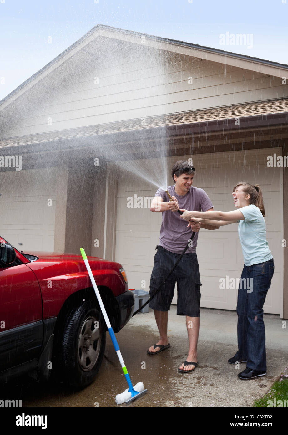 USA, Oregon, Ashland, young couple washing car in front of garage - Stock Image