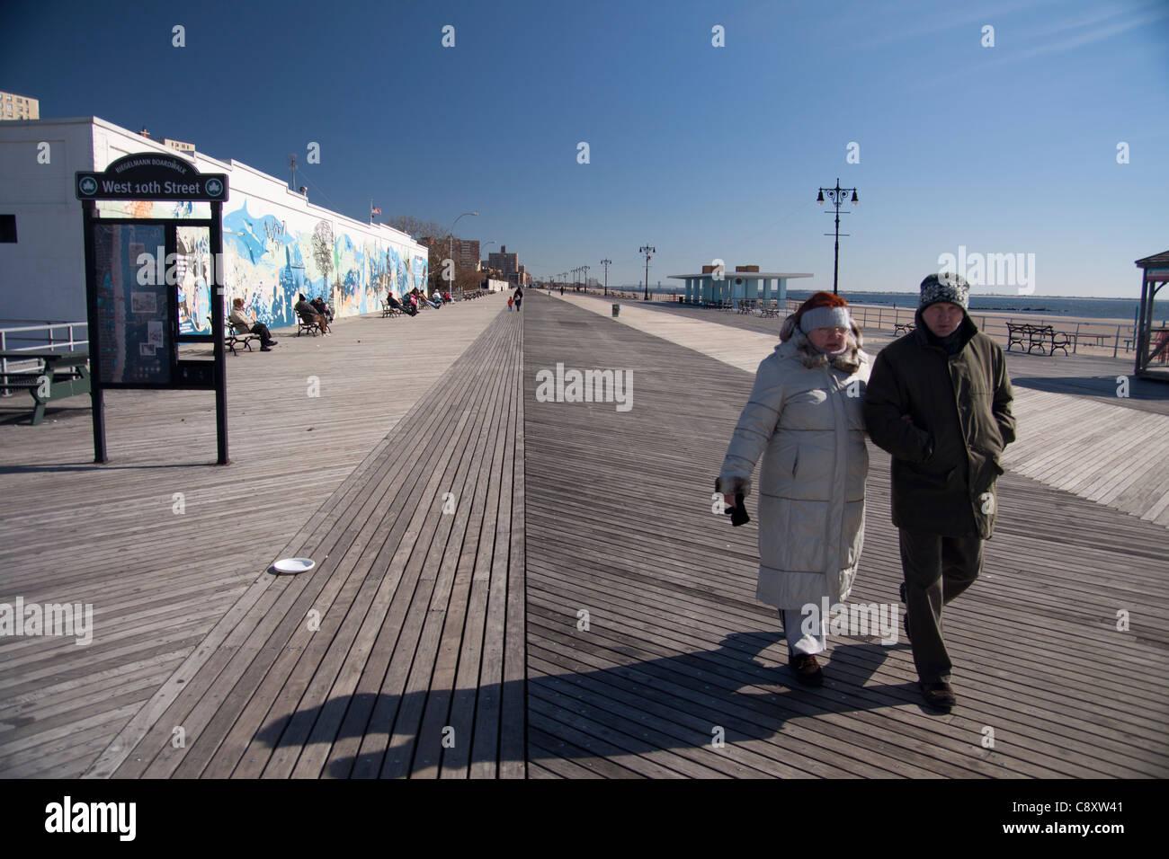 A couple walk along the boardwalk at Coney Island, New York city. - Stock Image