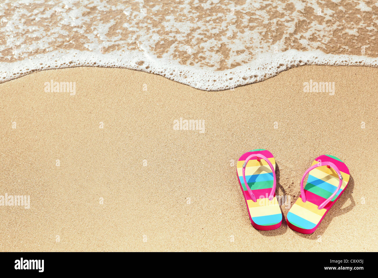 Tropical vacation concept--Flipflops on a sandy ocean beach - Stock Image