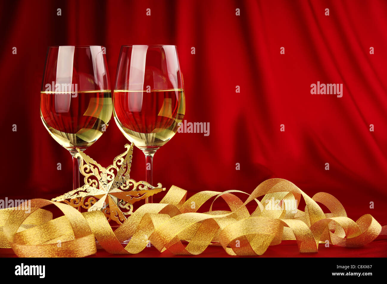 Glasses of champagne with golden ribbon. - Stock Image