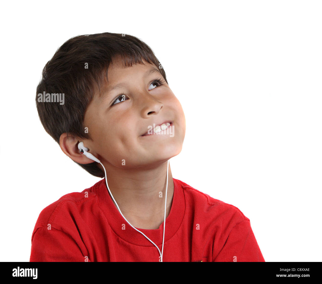 Young smiling happy boy with headphones on white background with copy space to right - Stock Image