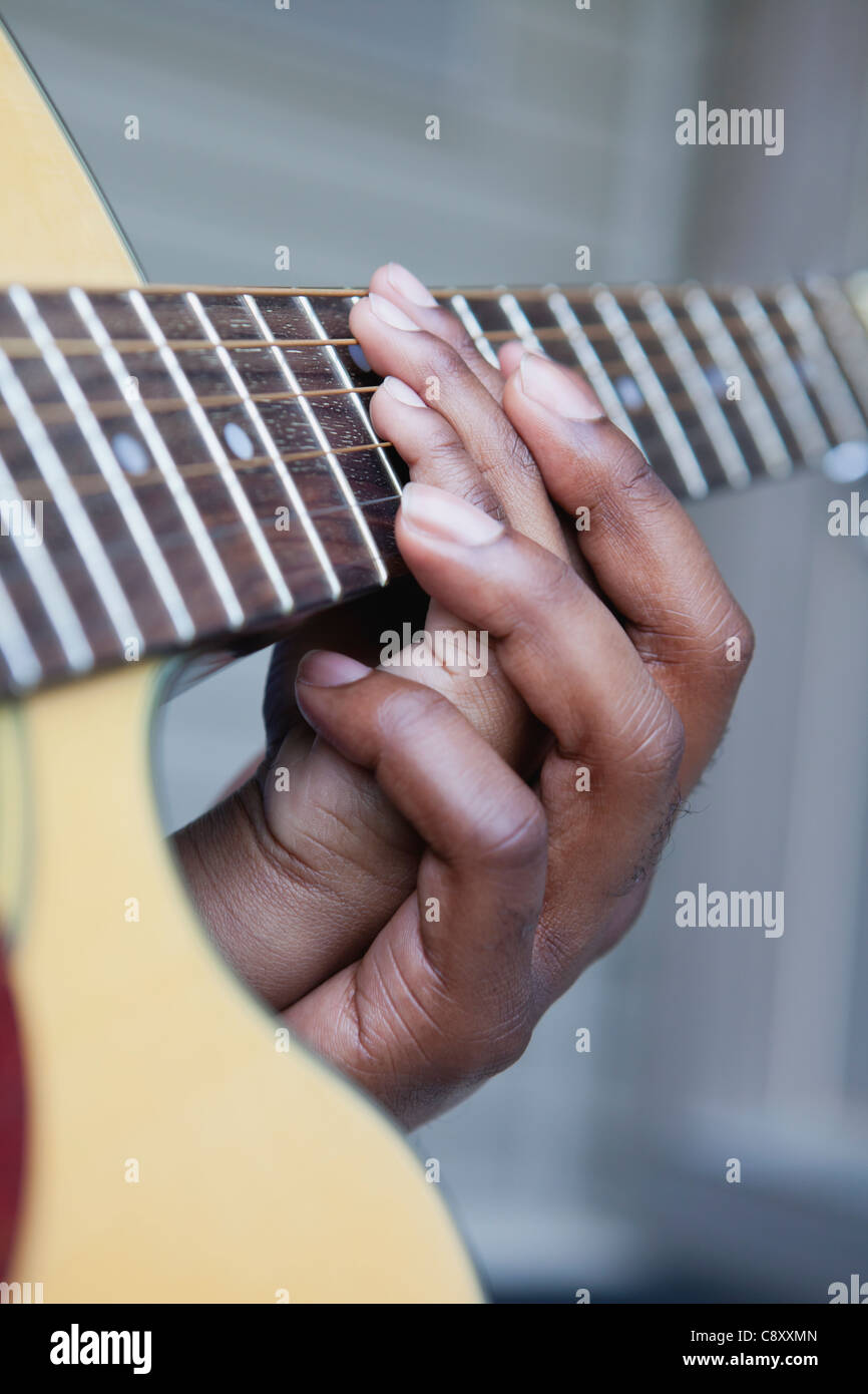 USA, Illinois, Metamora, Fathers and son (6-7) hands on guitar's neck - Stock Image