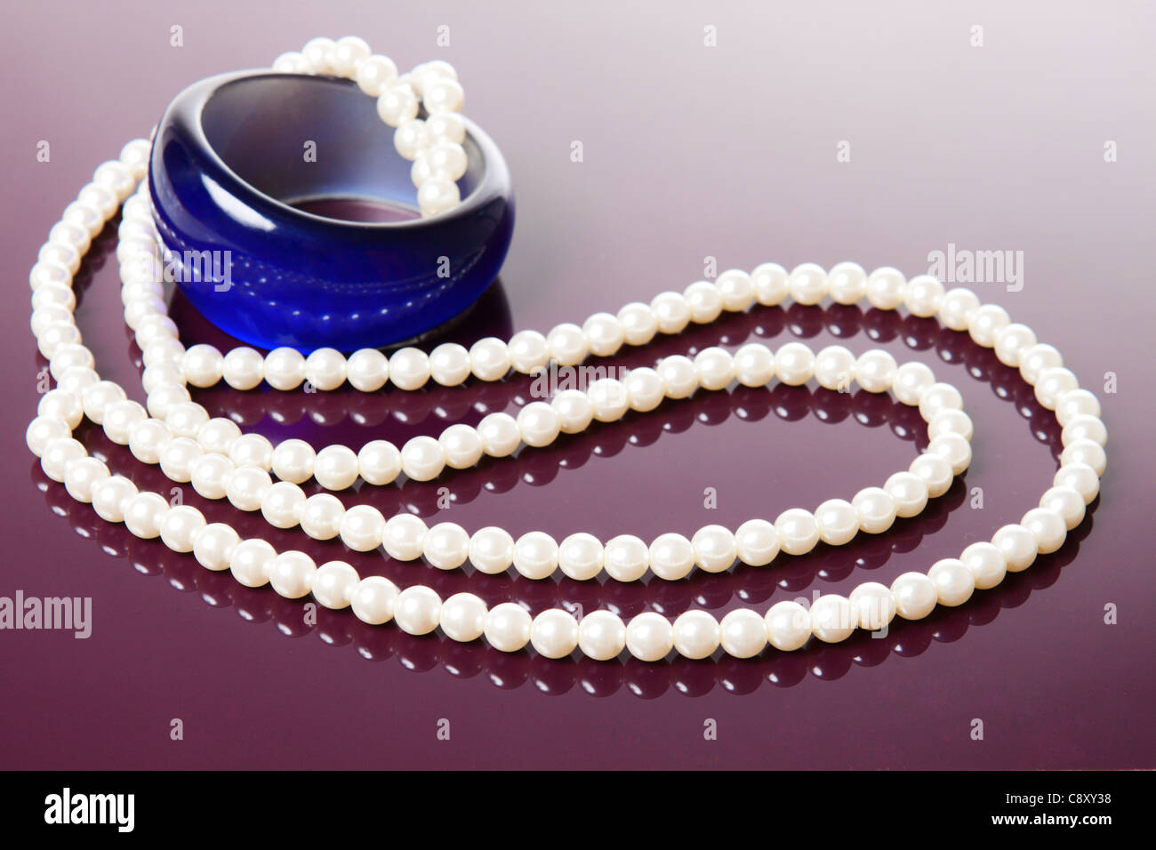 Pearl necklace and blue bracelet over glossy purple background - Stock Image