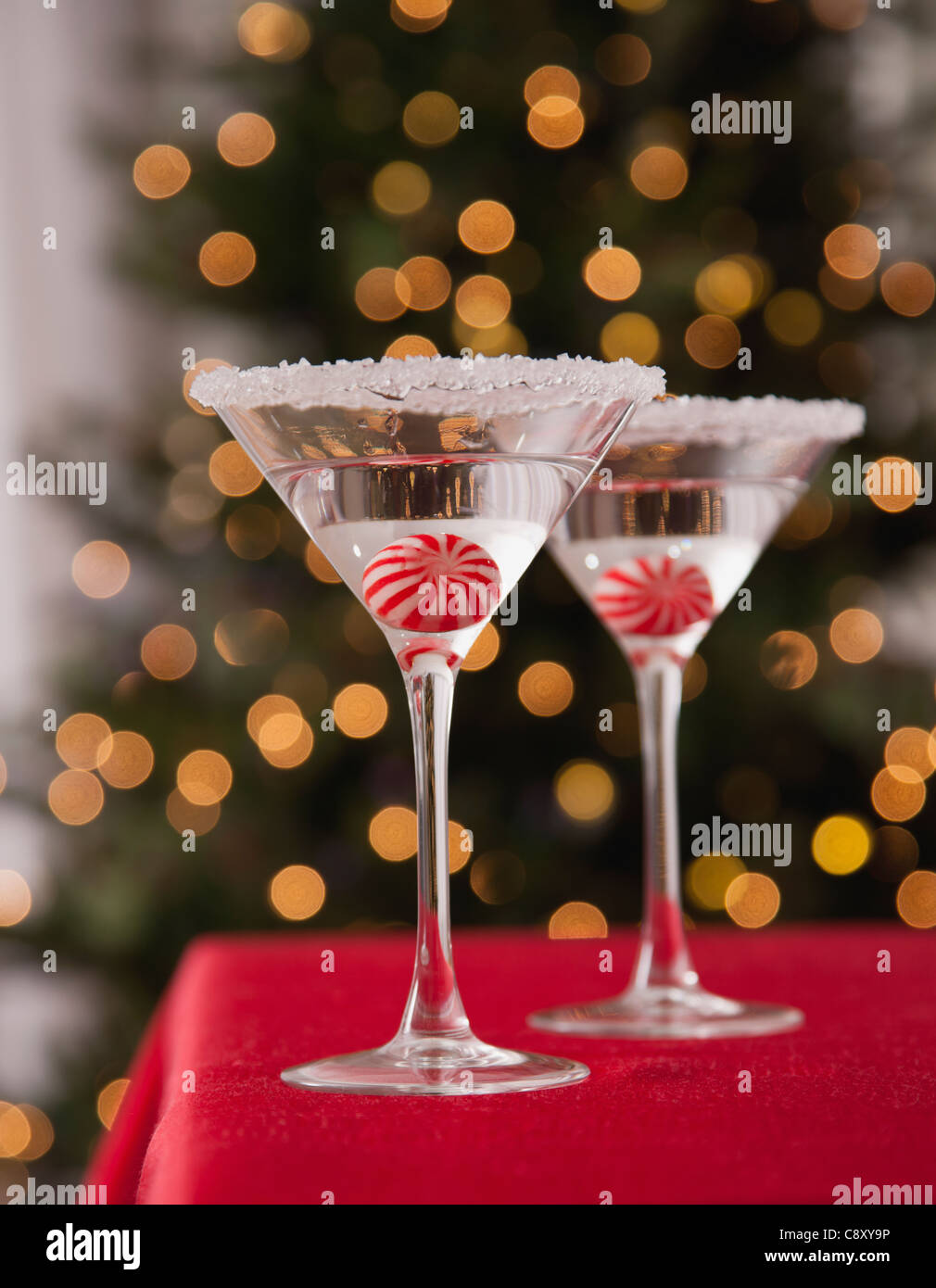 USA, Illinois, Metamora, Martini glasses with candies inside against illuminated Christmas tree - Stock Image