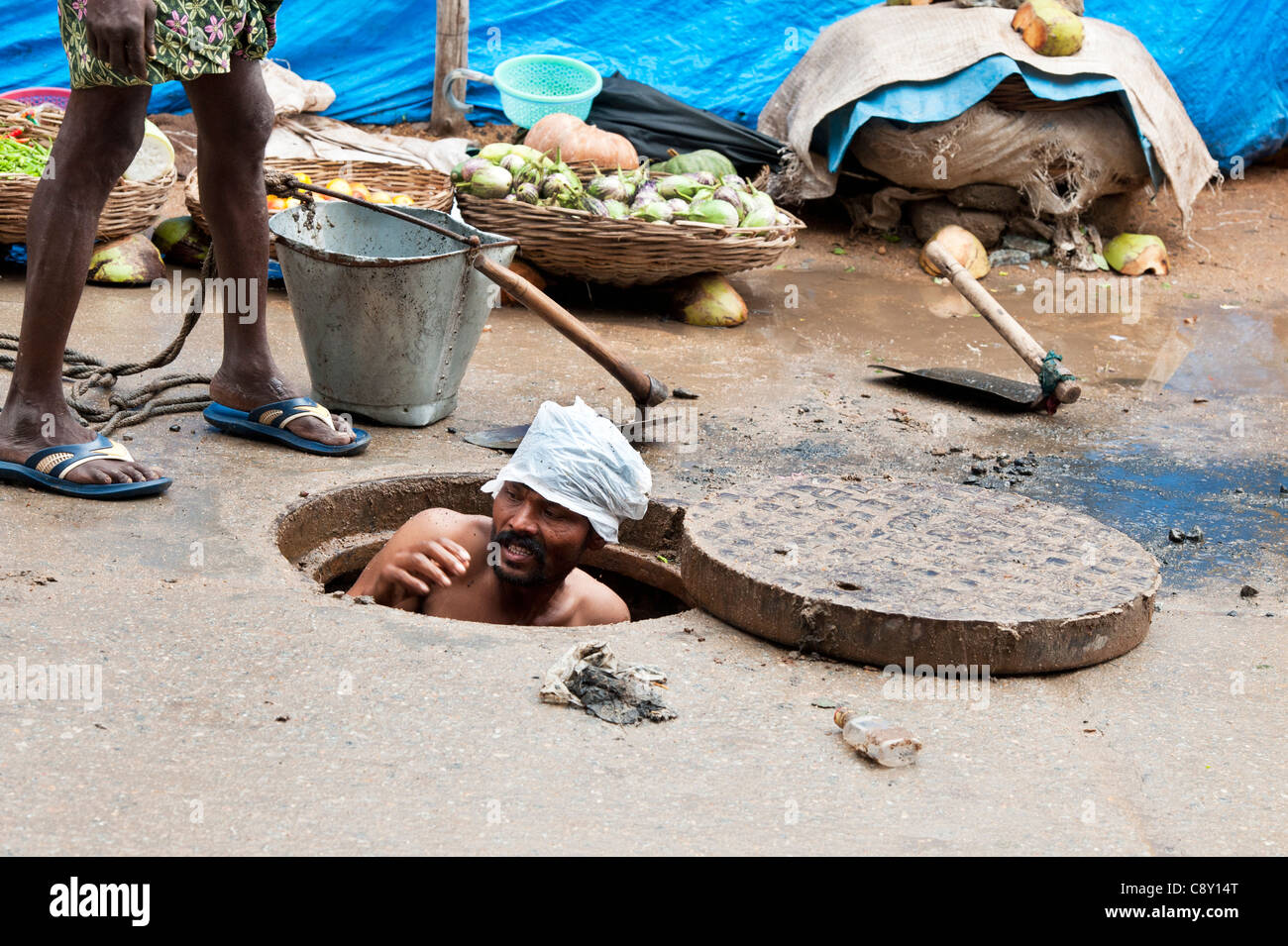 Indian sewage worker coming up from unblocking drains in the street. Puttaparthi, Andhra Pradesh, India - Stock Image