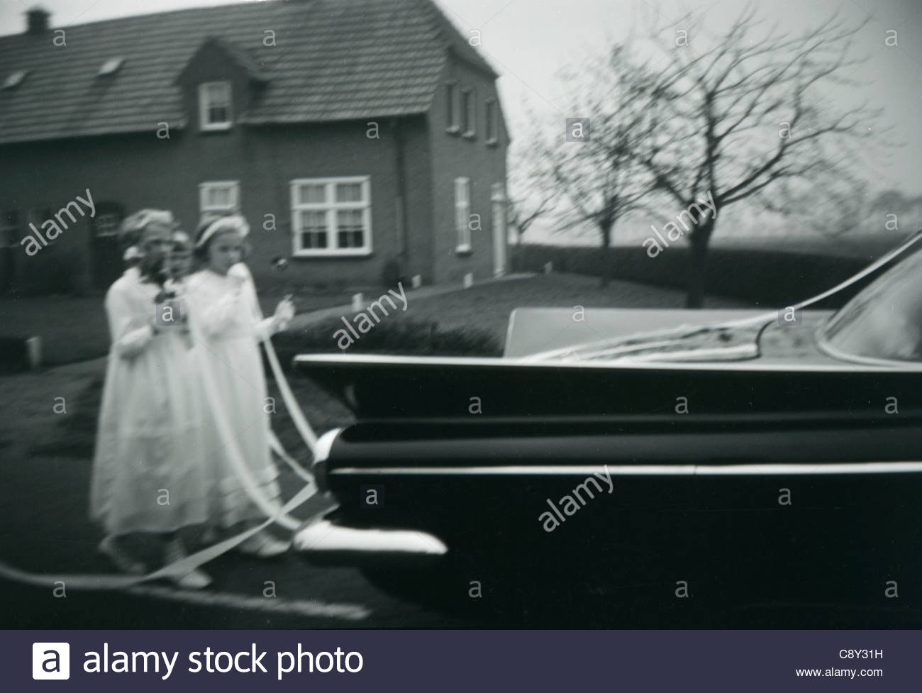 Brides maids following the brides and grooms wedding car - Stock Image