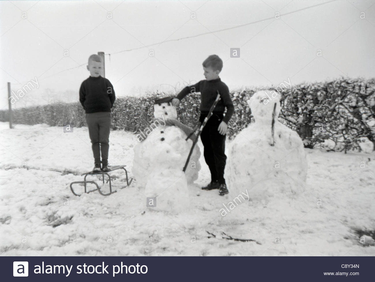 Two children with there snowmen - Stock Image