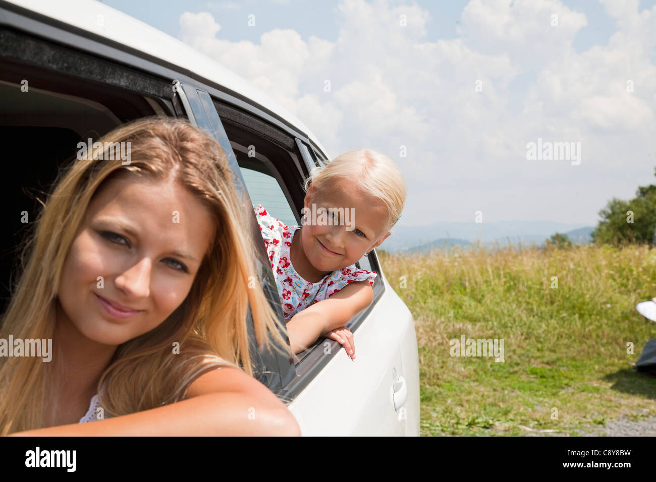 portrait of young woman and daughter looking out of car window - Stock Image