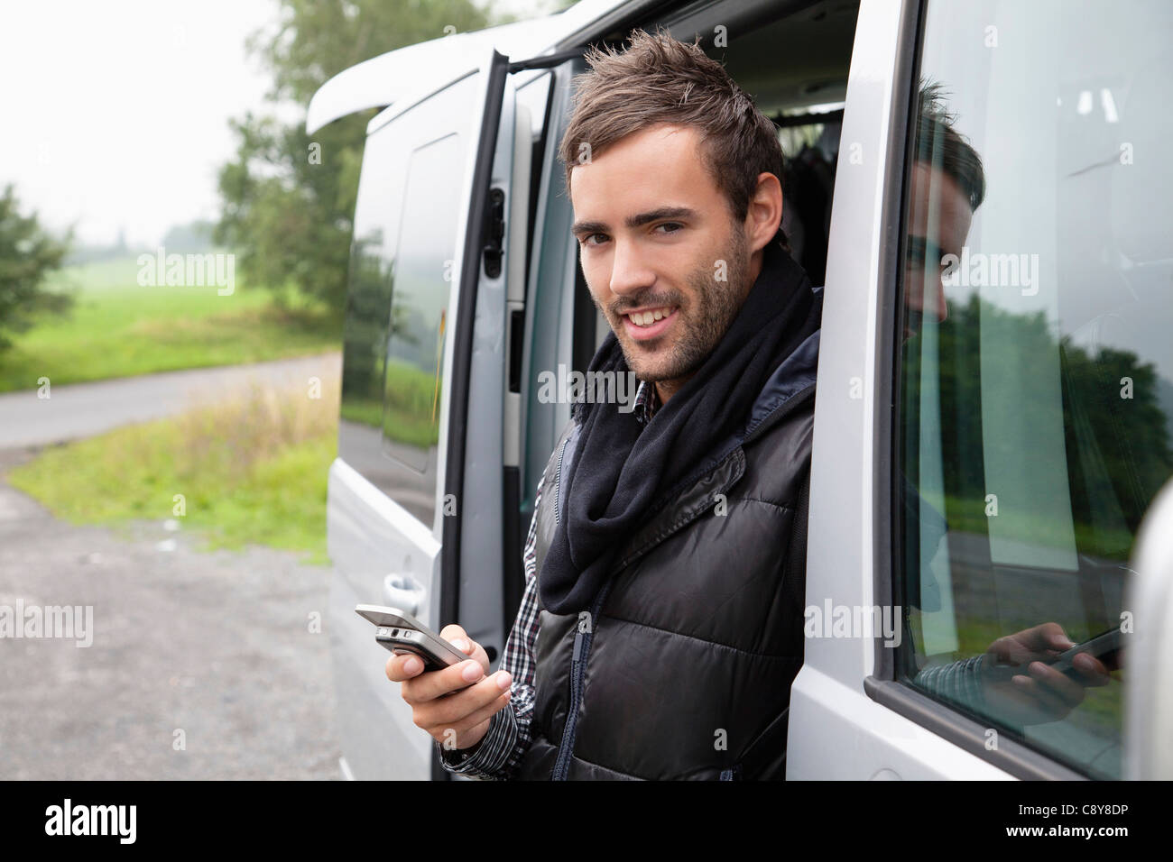 portrait of young man looking out of car window writing text message on mobile phone - Stock Image